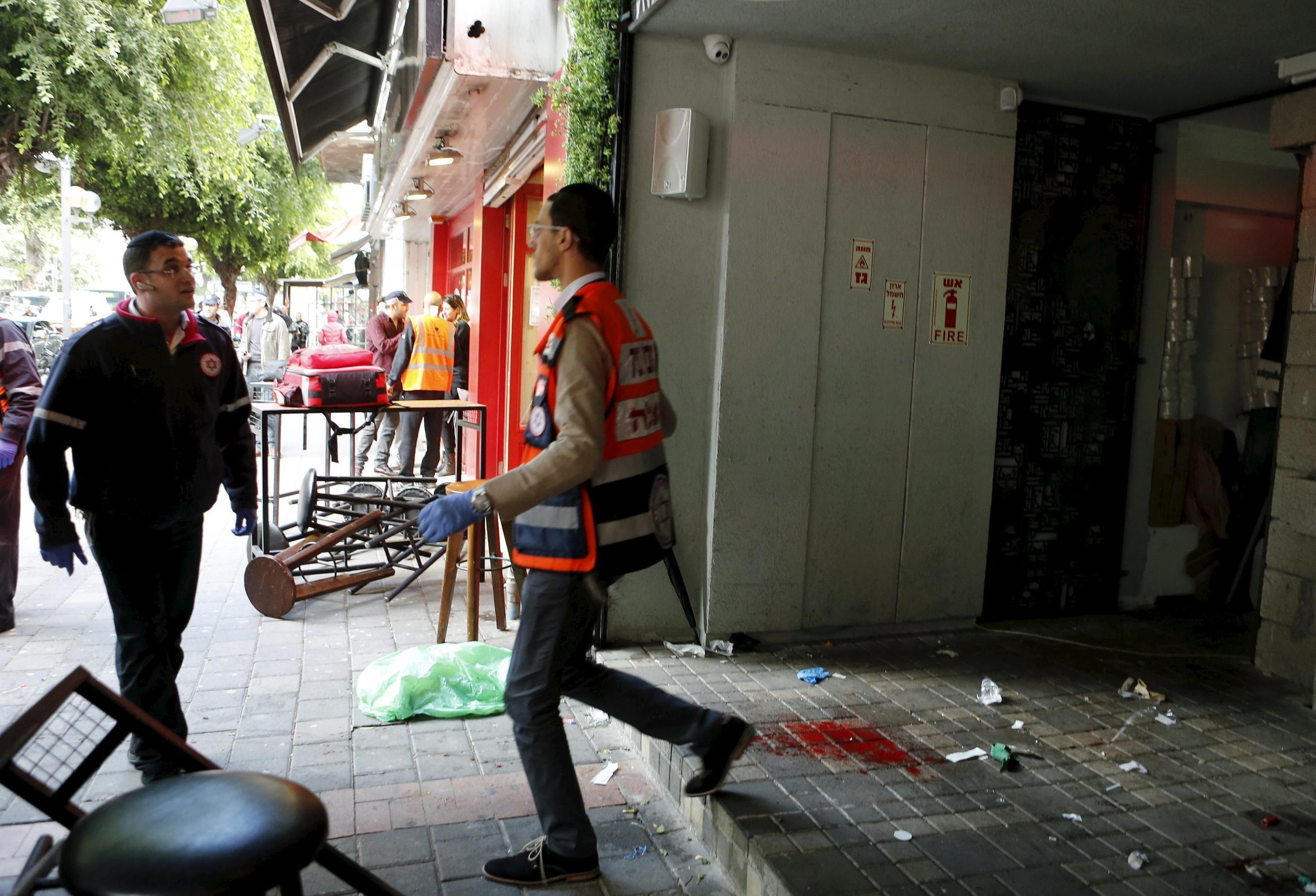Rescue personnel walk next to blood stains at the scene of a shooting incident in Tel Aviv, Israel on 1 January, 2016.
