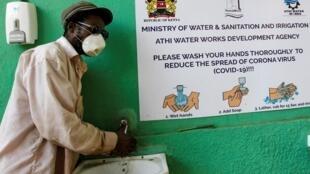 Un homme se lave les mains avec du savon et de l'eau à l'extérieur d'un marché de détail, à Nairobi, Kenya, le 2 avril 2020.