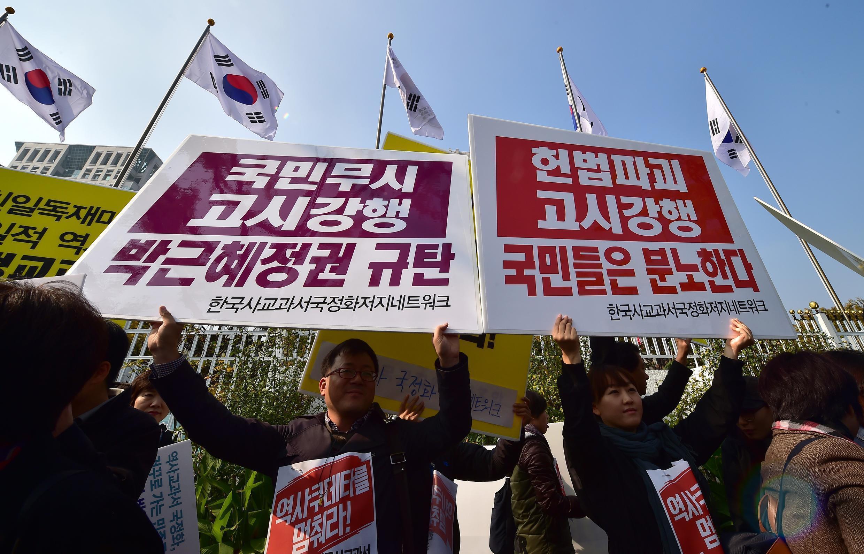 Des manifestants contre l'imposition de manuels d'histoire rédigés par l'Etat, le 3 novembre 2015 à Séoul. On peut lire sur les panneaux « Colère publique contre les politiques publiques allant contre la constitution ».