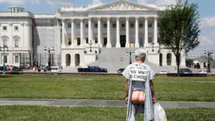 Un homme manifeste, le 21 juin 2017, à l'extérieur du Sénat contre le projet de réforme du système de santé des Républicains.