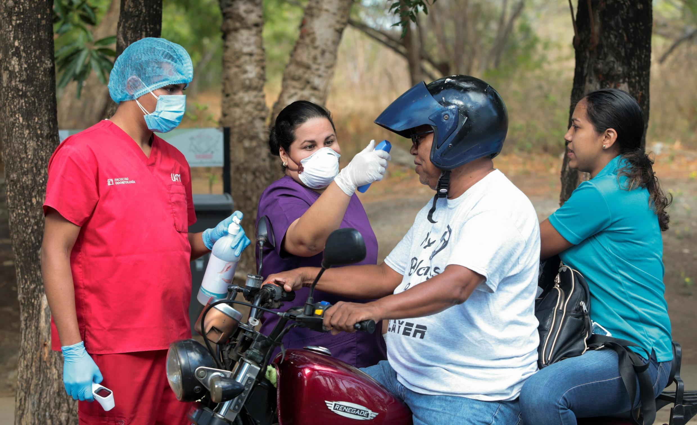 Une femme vérifie la température d'un homme à l'entrée d'une université à Managua, le 19 mars 2020 (image d'illustration).
