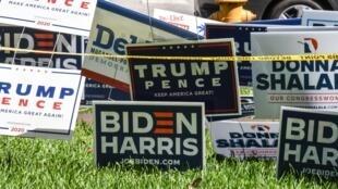 Des pancartes de Trump-Pence et de Biden-Harris sont déposées devant la pelouse d'une bibliothèque à Miami, en Floride le 27 octobre 2020.