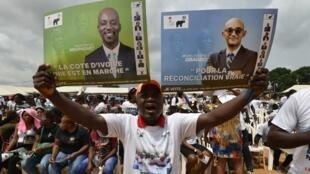 Un Ivoirien brandit deux pancartes, l'une de Michel Gbagbo, fils de Laurent Gbagbo, et l'autre Augustin Dia Houphouët, petit fils de Félix Houphouët-Boigny, alliés pour les législatives du 6 mars à Yopougon, le 27 février 2021.