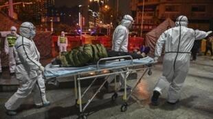 Des membres du personnel médical arrivent avec un patient à l'hôpital de la Croix-Rouge de Wuhan, le 25 janvier 2020.