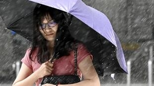Une femme se protége de la pluie et des vents intenses à Nouveau Taipei alors que le Typhon Lekima est passé au Nord-Est de Taiwan le 9 août 2019