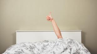 Femme dans un lit, pouce en l'air