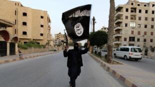 Un miembro del grupo yihadista Estado Islámico con una de sus banderas en la localidad siria de Raqa