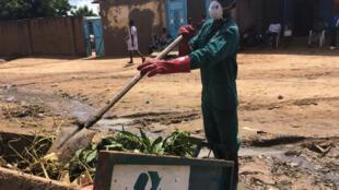 Djimasbé récolte les ordures ménagères et les dépose dans sa charrette. La gestion des déchets est un défi majeur pour N'Djamena.
