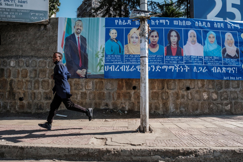 Un hombre pasa frente a carteles electorales del primer ministro Abiy Ahmed, en Adís Abeba, Etiopía, el 20 de abril de 2021