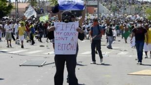 Un manifestante muestra una pancarta con una consigna contra la FIFA, en las cercanías del estadio Castelao, en Fortaleza, el 19