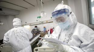 Un médico atiende a un paciente en un hospital de la provincia de Hubei en China, epicentro de la epidemia de coronavirus. 13 de febrero de 2020.