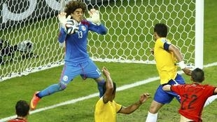 Mexico's Guillermo Ochoa (L) deflects the ball during a goal attempt by Brazil's Thiago Silva (top R)