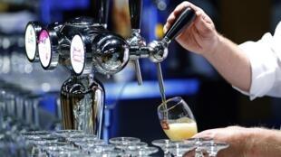 Barman serve creveja do grupo AB InBev em Bruxelas, em 2015