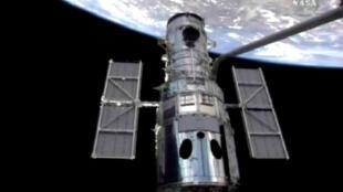 Le téléscope spatial Hubble, attaché au bras robotisé de la navette Atlantis et la terre en arrière-plan, le 13 mai 2009.