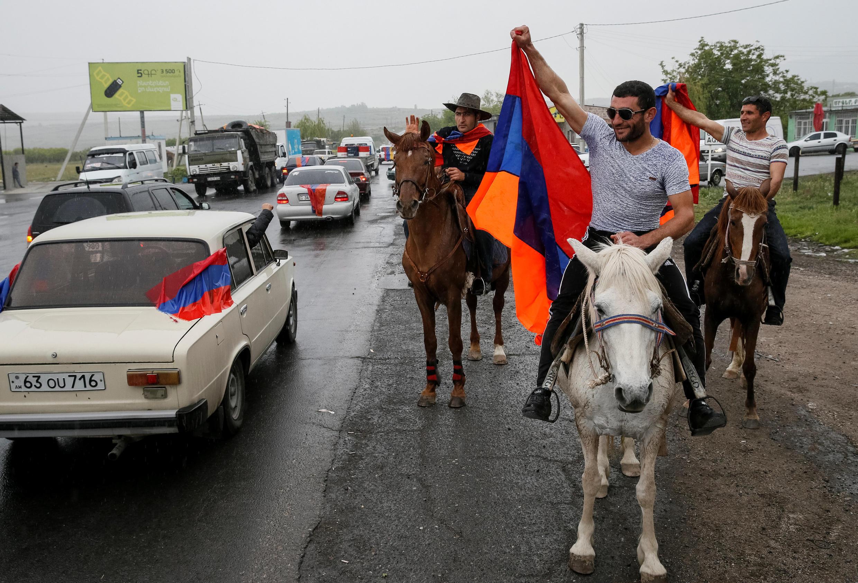 Местные жители приветствуют с флагами сторонников Никола Пашиняна по дороге из Еревана в Гюмри, 27 апреля 2018 года.
