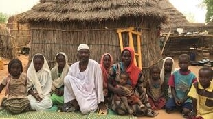 Hamis Yahya Yusuf, 48, from Amshoka village, Darfur, in front of his hut in Djabal refugee camp, eastern Chad, with his wife and children