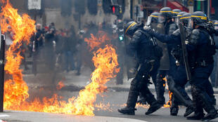 French CRS riot police protect themselves from flames during clashes at the traditional May Day labour union march in Paris, France, May 1, 2017.