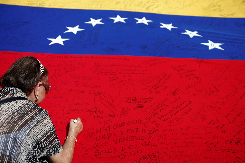 Người ủng hộ đối lập Venezuela ký tên lên quốc kỳ  và đòi tổ chức trưng cầu dân ý về phế truất  tổng thống Nicolas Maduro, tại Caracas, ngày 06/06/2016.