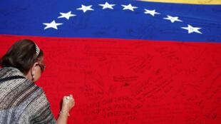 Opositor escreve mensagem na bandeira da Venezuela durante evento em apoio a um referendo para destituir Nicolás Maduro.