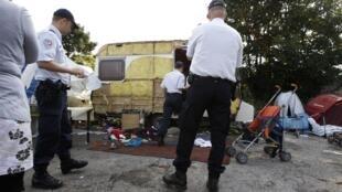 Des policiers recensent les habitants d'un camp illegal de Roms à Saint-Andre-les-Lille, le 9 août 2010. Les évacuations se succèdent à travers la France, sans que des solutions de relogement ne soient proposées.