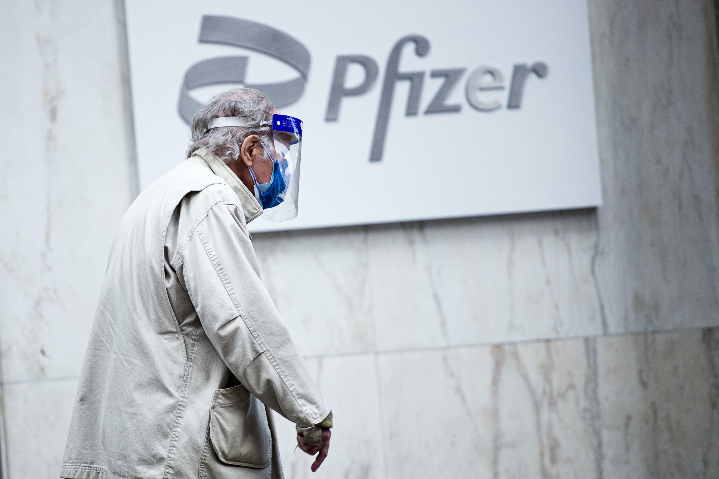 A man wearing facemask and shield walks past the Pfizer headquarters in New York