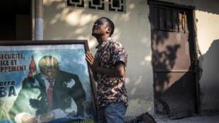 Mfuasi wa Jean-Pierre Bemba akiomba mbele ya picha ya aliyekuwa makamu wa rais wa DRC kwenye makao makuu ya chama cha MLC huko Kinshasa Juni 8, 2018.