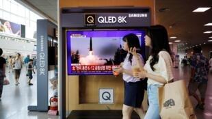 À Séoul, le 6 août, deux femmes passent devant une télévision montrant les tirs de missiles nord-coréens.