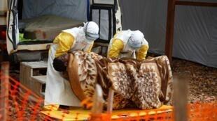Des employés du centre Ebola de Butembo prennent en charge une femme atteinte d'Ebola, le 28 mars 2019.