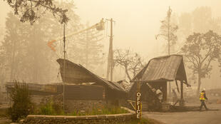 Des ouvriers réparent le système d'électricité à Mill City, dans le nord de l'Oregon, le 13 septembre 2020. Les flammes ont forcé l'évacuation de 40 000 habitants.