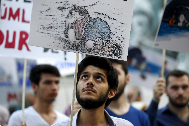Un manifestante turco en Estambul con un dibujo representando al pequeño Aylan Kurdi, que murió ahogado intentando atravesar el mar Egeo.