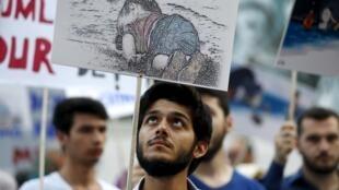Un manifestante turco en Estambul lleva una pancarta con un dibujo representando a Aylan Kurdi.