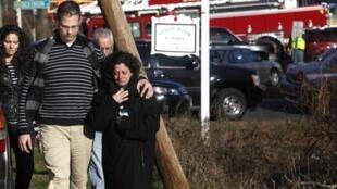 Des familles quittent le lieu de la fusillade à Newtown, le 14 décembre 2012.