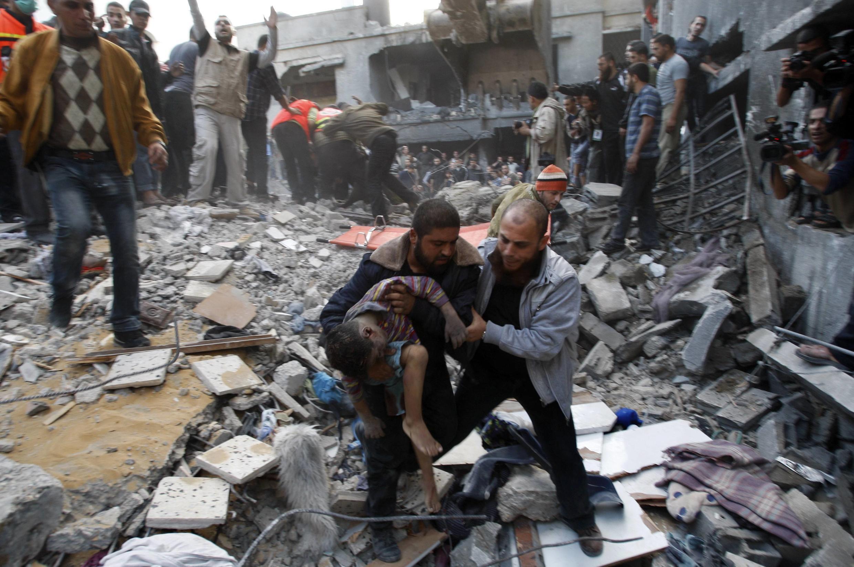O corpo de uma criança é retirado dos escombros de uma casa em Gaza, após ataque israelense.