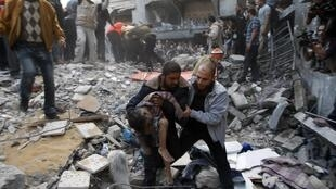 Palestinians carry the dead body of a child from under the rubble of a house after an Israeli air strike in Gaza City