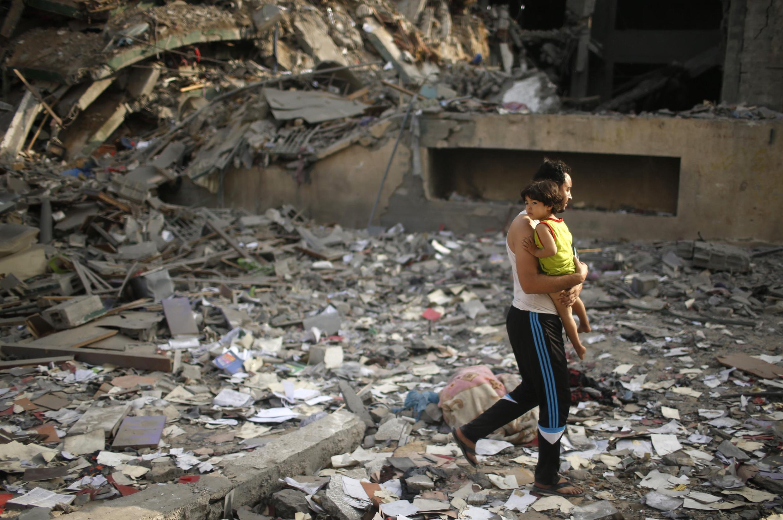 Pai caminha com criança no colo sobre escombros de prédio destruído nesta terça-feira em Gaza