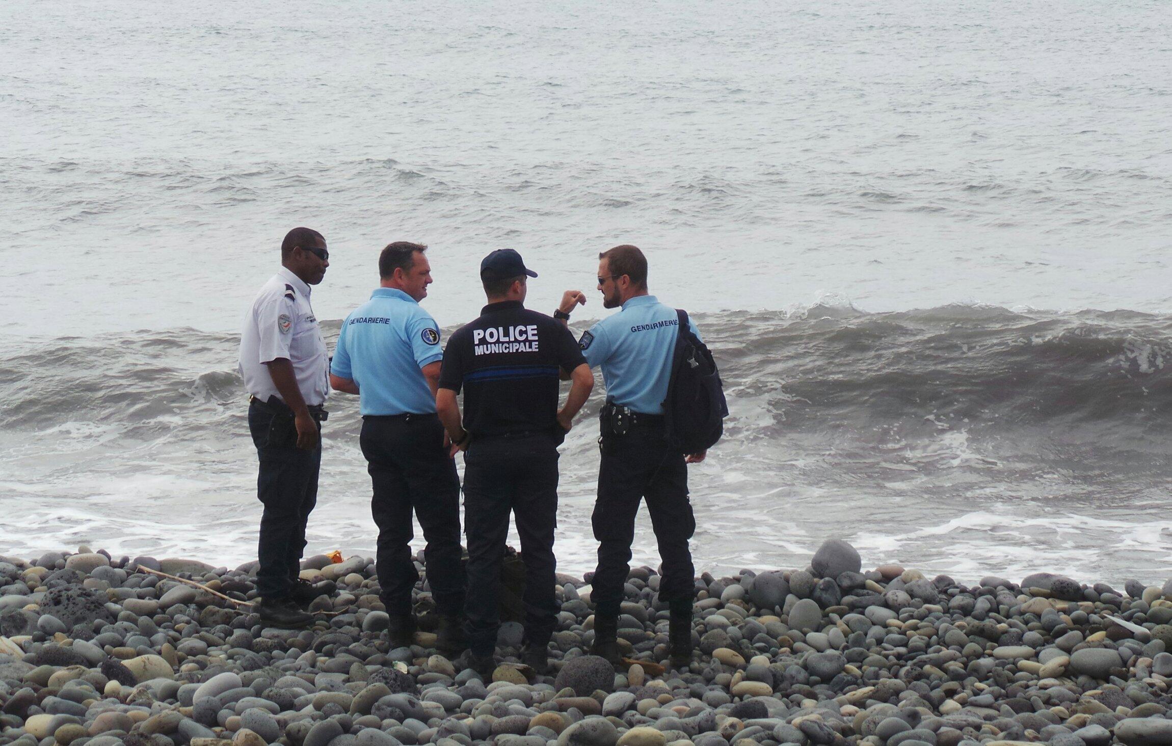 Investigadores franceses conversam na praia em que foi encontrado destroço, na Ilha da Reunião