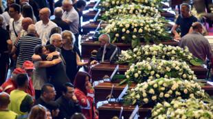 Caixões com os corpos de vítimas do desabamento da ponte Morandi enfileirados no centro de exposições de Gênova.