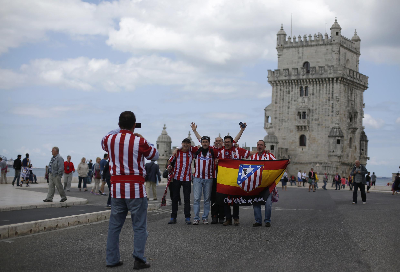 Torcedores do Atlético de Madrid posam para fotos em frente à Torre de Belém, em Lisboa.