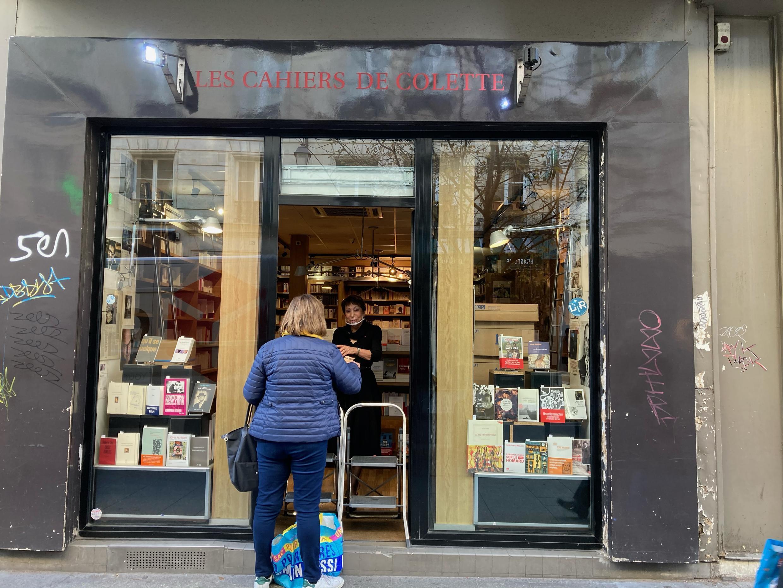 """Colette Kerber, da livrarria """"Les Cahiers de Colette"""", antende uma cliente que encomendou um livro pelo """"click&collect""""."""