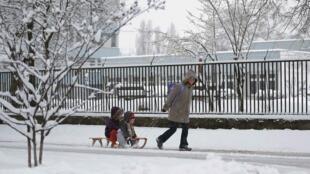 Mãe transporta filhos em trenó pelas ruas cobertas de neve em Budapeste (Hungria).