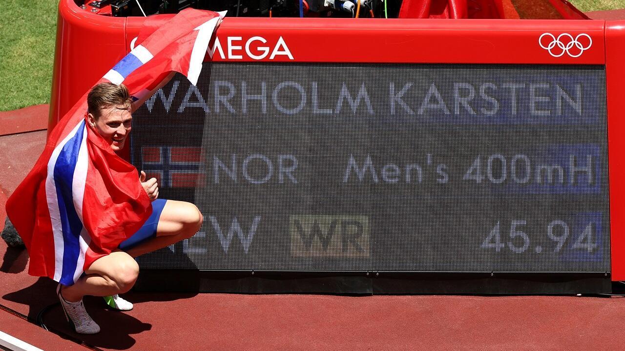 Le Norvégien Karsten Warholm prend la pose à côté du chronomètre de son record du monde du 400m haies, le 3 août 2021 à Tokyo.