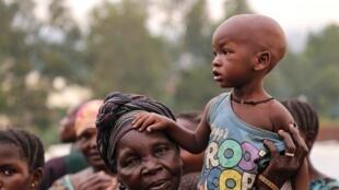 Une femme porte un enfant sans un camp de déplacés de la ville de Bunia, en Ituri, le 21 juin 2019.