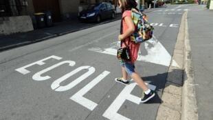Une écolière traversant la route à Verquin, dans le Pas-de-Calais, la veille de la rentrée scolaire.