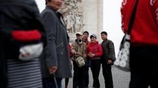 Des touristes chinois posent pour des photos devant l'Arc du triomphe sur les Champs-Élysées, pendant le 19ème acte des gilets jaunes, le 23 mars 2019. (photo d'illustration)