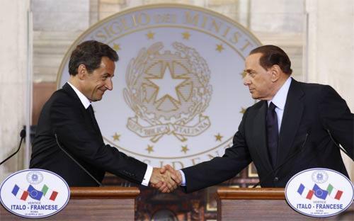 Berlusconi (R) and Sarkozy shake hands during a post-summit news conference at Rome's Villa Madama