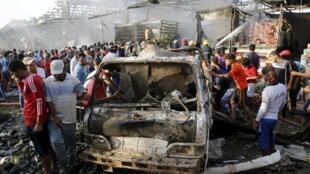 Coches incendiados tras el atentado en Sadr City (Bagdad) este jueves en Iraq.