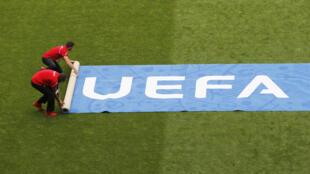 Wafanyakazi wa Uefa wakitandaza uwanjani moja ya bango la shirikisho la mpira Ulaya