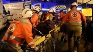 Bombeiros carregam uma pessoa ferida no atentado ao Bataclan