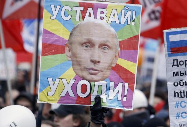 """Một người biểu tình tại Nga hôm 24/12/2011 giơ cao tấm biển có hình Putin và hàng chữ """"Cút đi""""."""