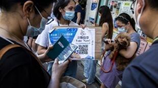 Une volontaire présente une pancarte avec un QR code à scanner pour voter aux primaires pan-démocrates à Hong Kong, le 12 juillet 2020.